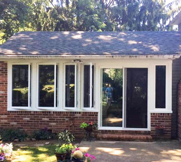Exterior view of brick porch with new vinyl casement windows and sliding patio door