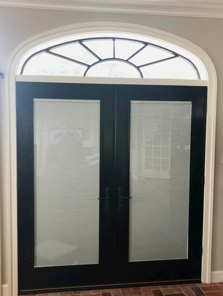 Interior view of black wood double French doors with transom window