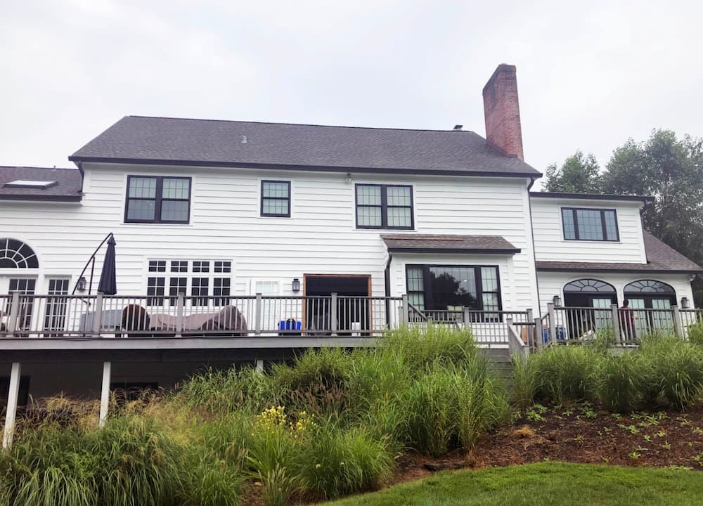 Rear exterior view of white colonial home with black windows
