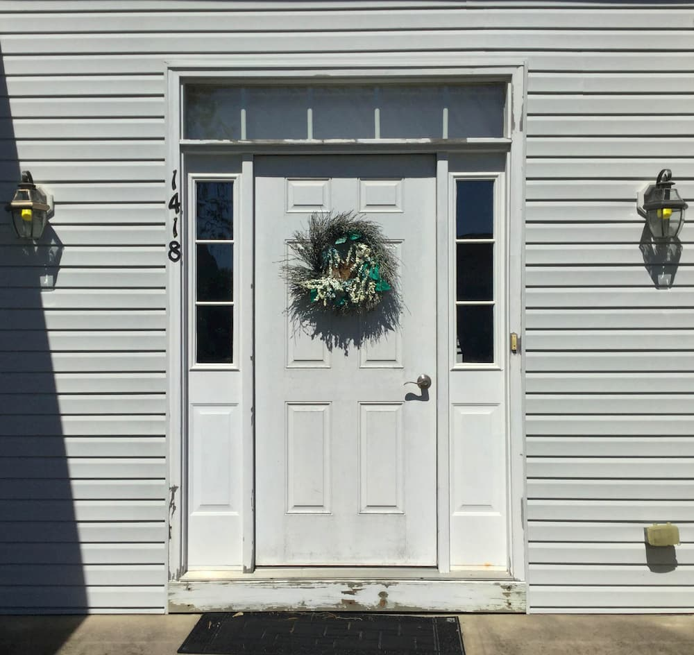 Exterior view of old white front entry door with sidelights and transom