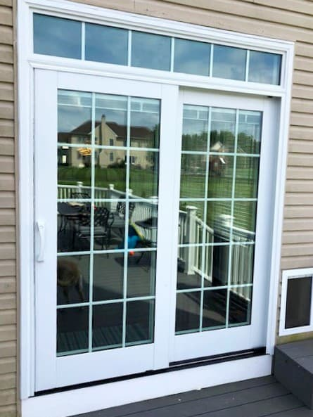 Exterior view of new white wood sliding patio door with transom.
