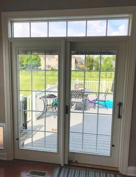 Interior view of new white wood sliding patio door with transom window and traditional grilles.