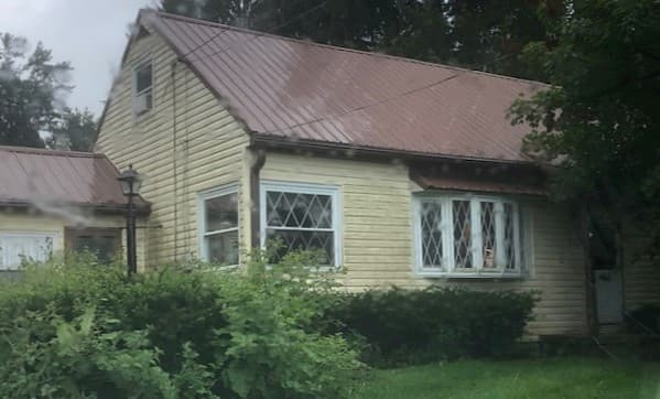 Exterior view of yellow home with old windows