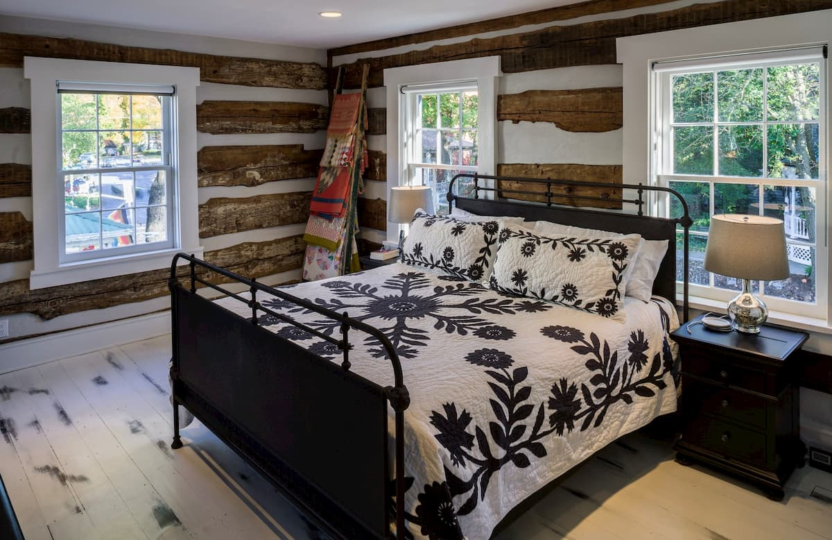 Interior view of rustic bedroom with white wood double-hung windows with traditional grille patterns