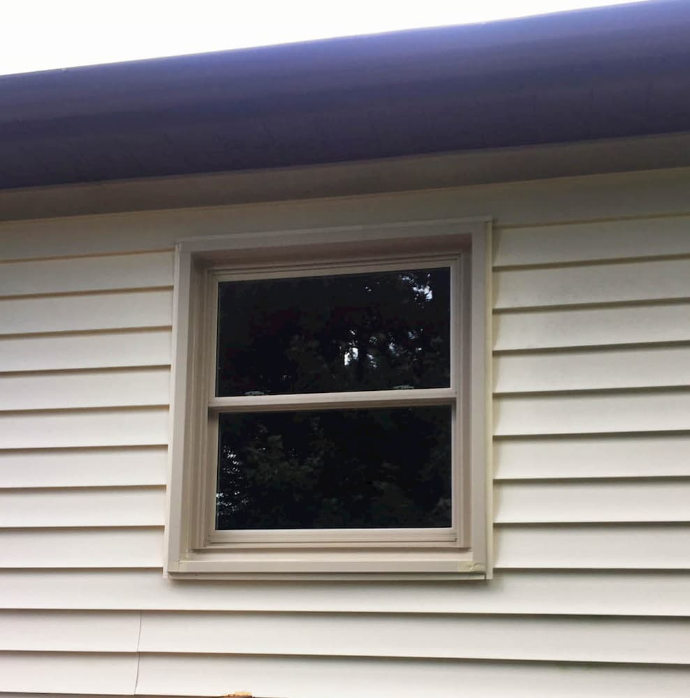 New vinyl double-hung window on home with beige siding