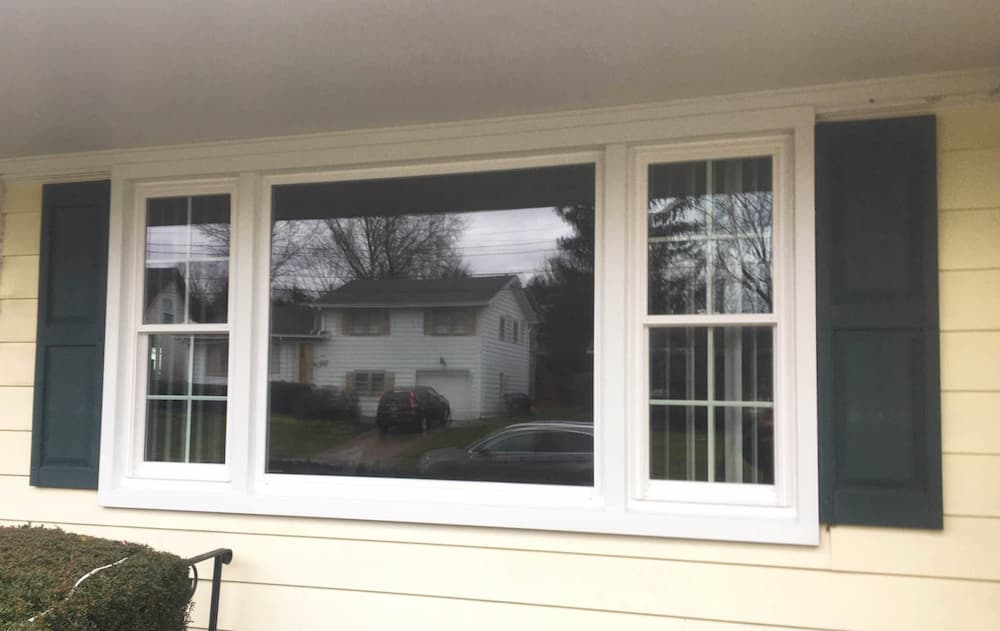 Exterior view of white vinyl fixed and double-hung windows on a yellow home