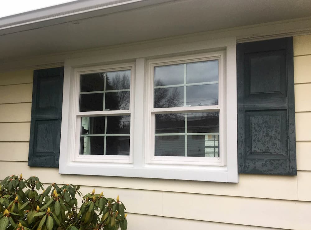 Exterior view of new vinyl double-hung windows with traditional grille profiles on a yellow home