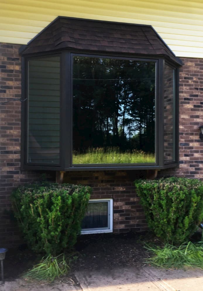 Exterior view of new wood bay window with black finish on a brick home