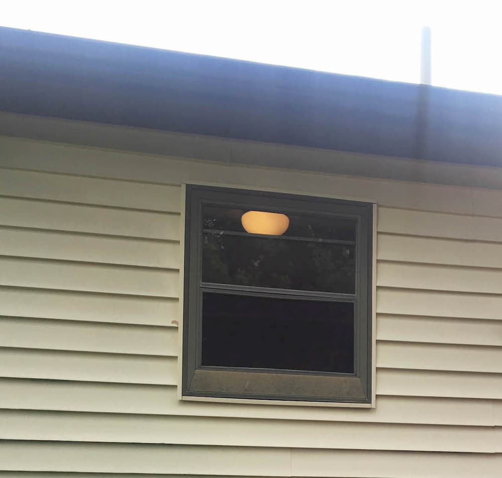 Old double-hung window on home with beige siding