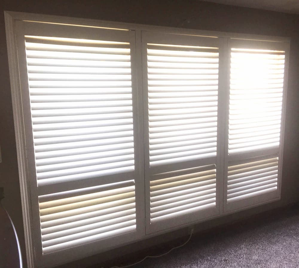 Interior view of three old windows covered with white blinds