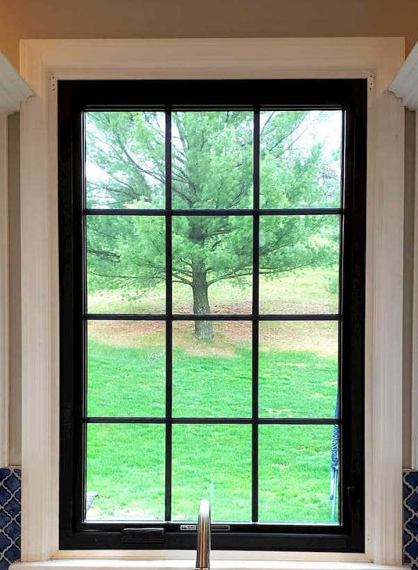 Black double-hung fiberglass window with traditional grille pattern above kitchen sink