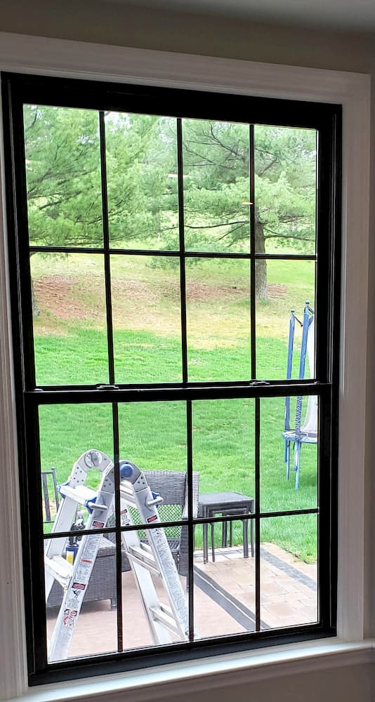 New large fiberglass double-hung window with traditional grille pattern and black finish