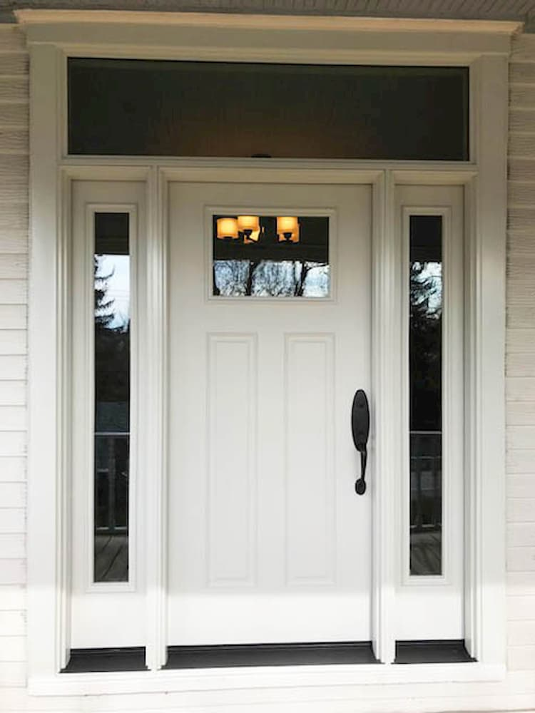 Front entry with white entry door, sidelights, and a transom window.