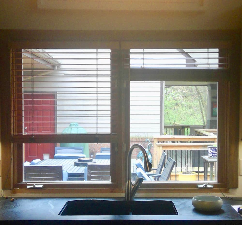 Interior view of old casement window with blinds over kitchen sink