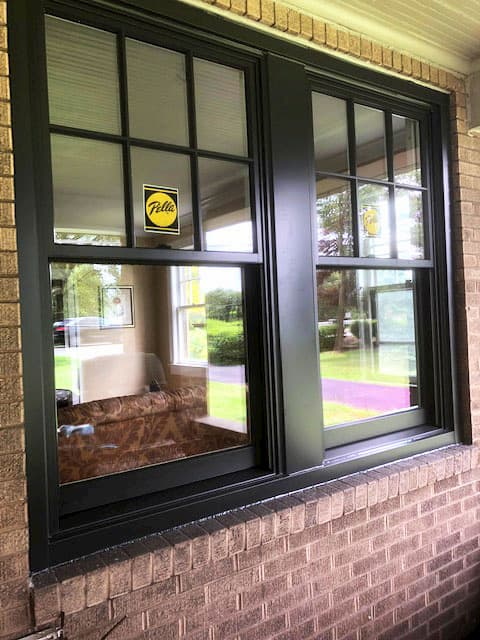 New wood black double-hung windows with traditional grille pattern on the upper sash