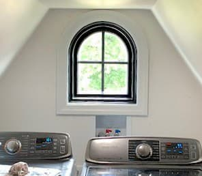 Custom black arch-shaped window in a laundry room