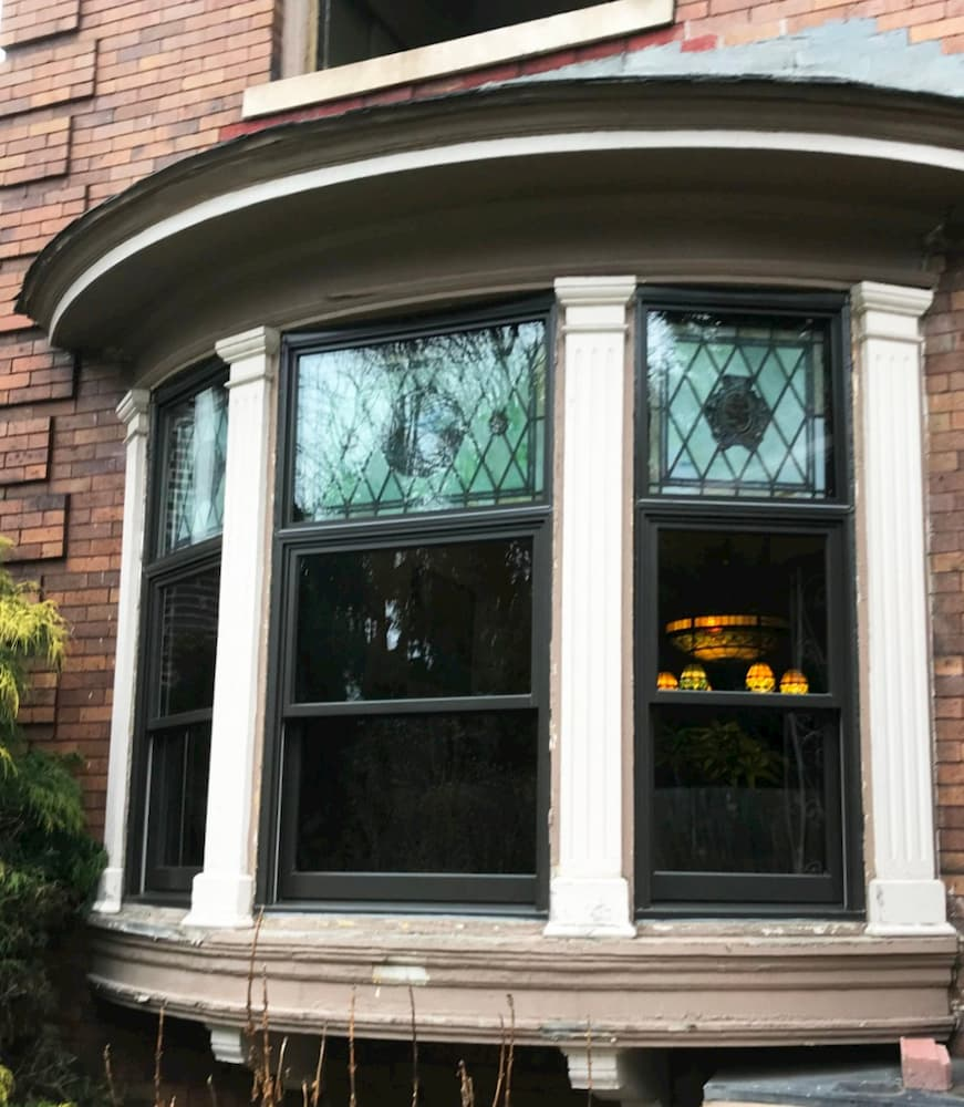 Exterior view of new wood bay window with stained glass in the upper sash