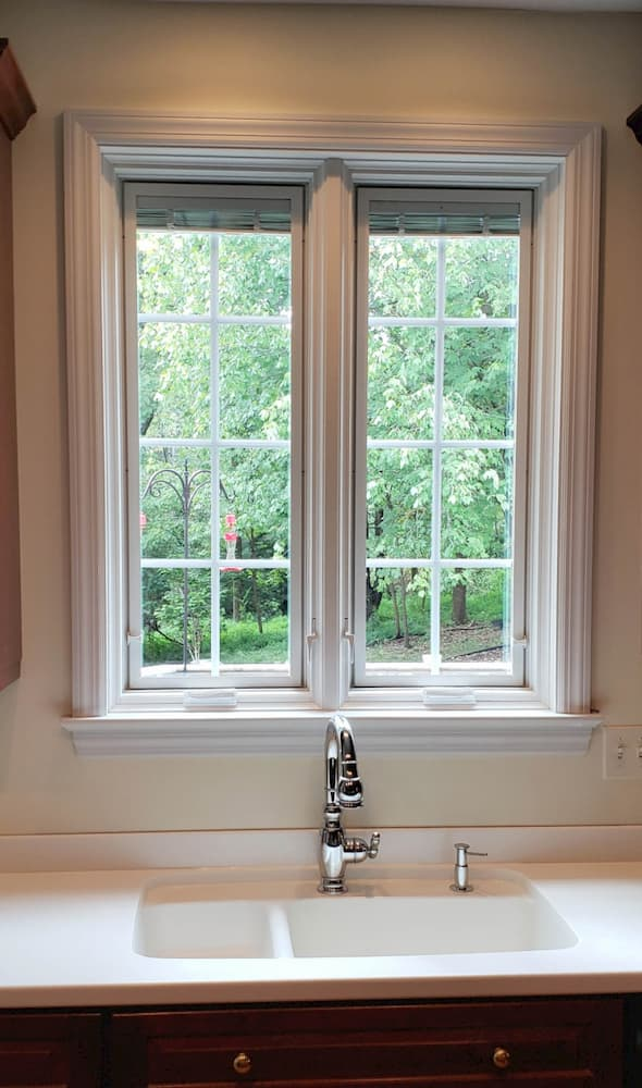 New wood casement windows with traditional grille patterns over kitchen sink
