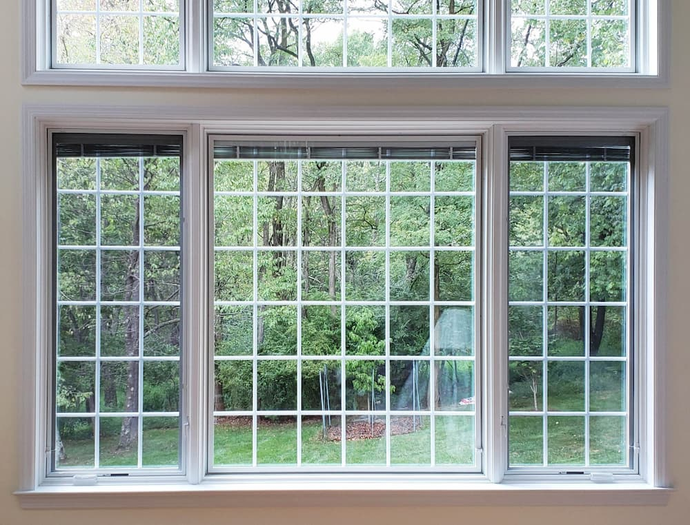 Fixed and casement wood windows with traditional grille patterns