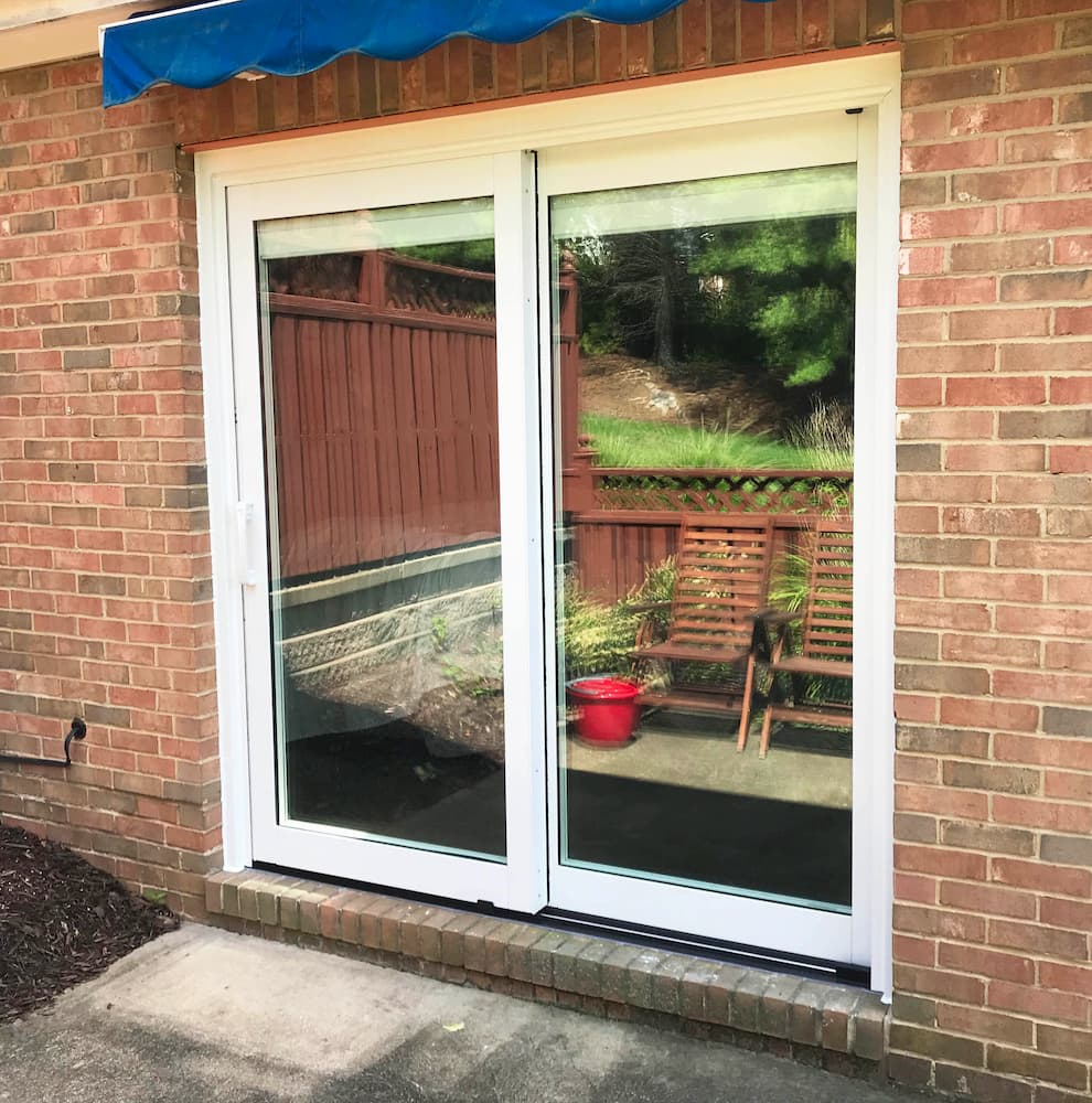 Exterior view of new white clad sliding patio door on red brick home