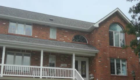 Exterior view of brick home with old windows