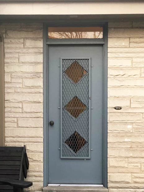 Old blue-gray back entry door with a transom window on a stone home