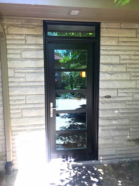 Back fiberglass entry door with contemporary grille pattern and a transom window
