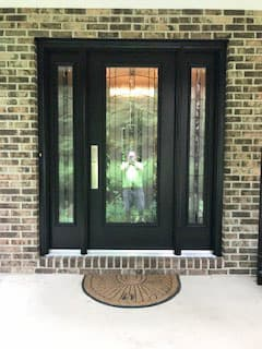 Black full-light wood entry door with full-length sidelights and decorative glass.