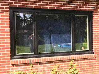 New black wood casement and fixed windows on red brick home