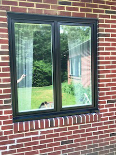 New black wood casement windows on red brick home