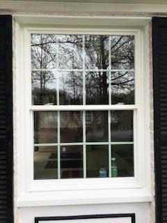 White fiberglass double-hung window with traditional grille pattern