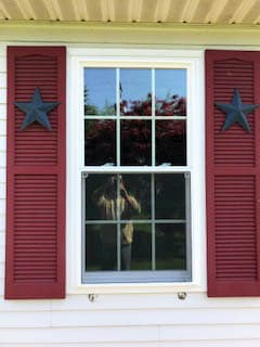 New vinyl double-hung window with traditional grille pattern and red shutters