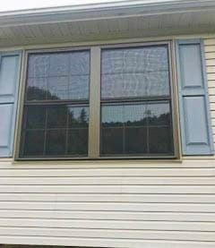 Exterior view of two new wood double-hung windows with traditional grille patterns