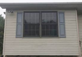 Exterior view of two new wood double-hung windows with traditional grille pattern