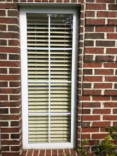 Old white casement window on red brick home