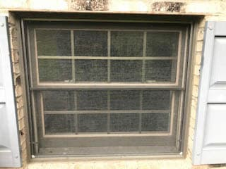 Exterior view of old brown double-hung window with screen