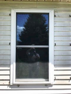Old double-hung window on home with white siding