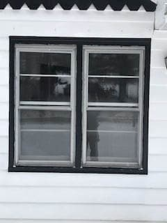 Exterior view of old double-hung windows against white siding