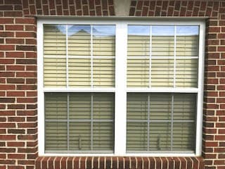 Old white double-hung windows on red brick home