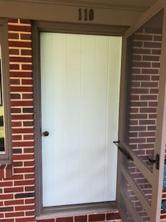 Old white entry door with brown storm door