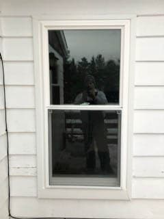 Exterior view of white vinyl double-hung window against white siding