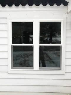 Exterior view of two white vinyl double-hung windows against white siding