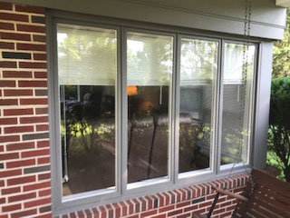 Casement windows on red brick home before replacement