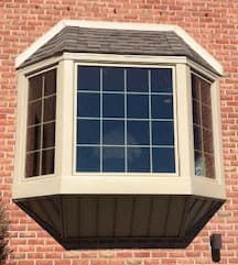 Exterior view of new wood bay window with traditional grille pattern on a red brick home
