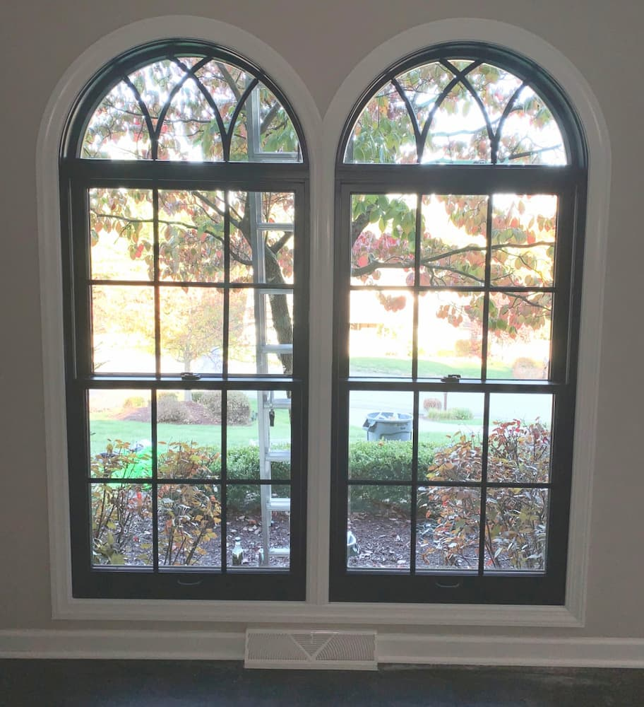 Interior view of black double-hung windows with traditional grille patterns and half-arch transoms