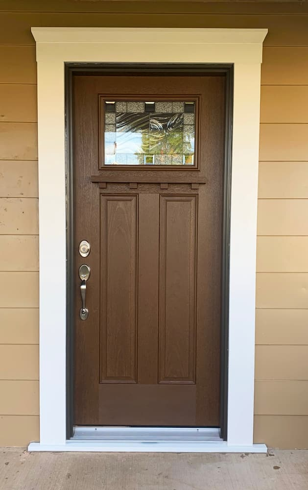 New wood-look Craftsman-style fiberglass entry door with decorative glass