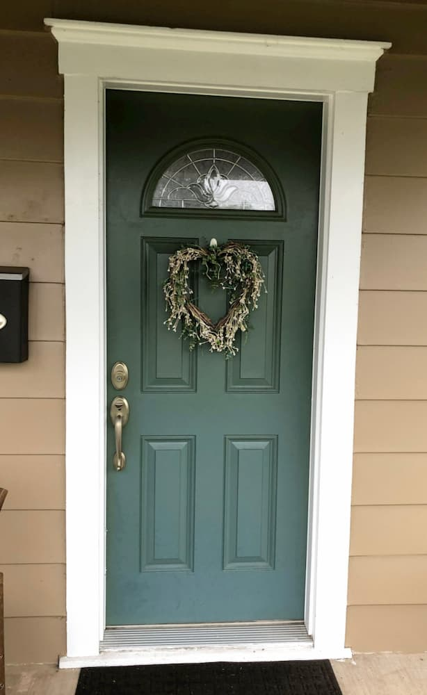 Old green entry door with wreath