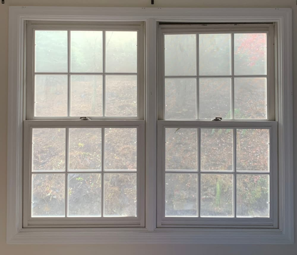 Interior view of old white double-hung windows with traditional grille pattern