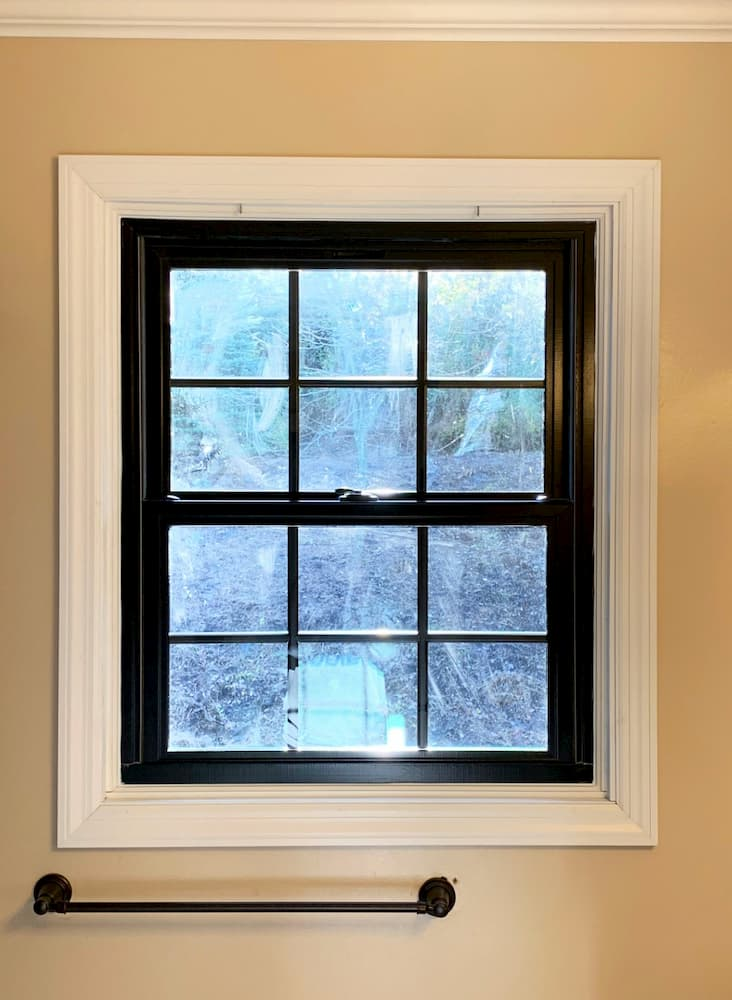 Black double-hung window with traditional grille pattern in a bathroom