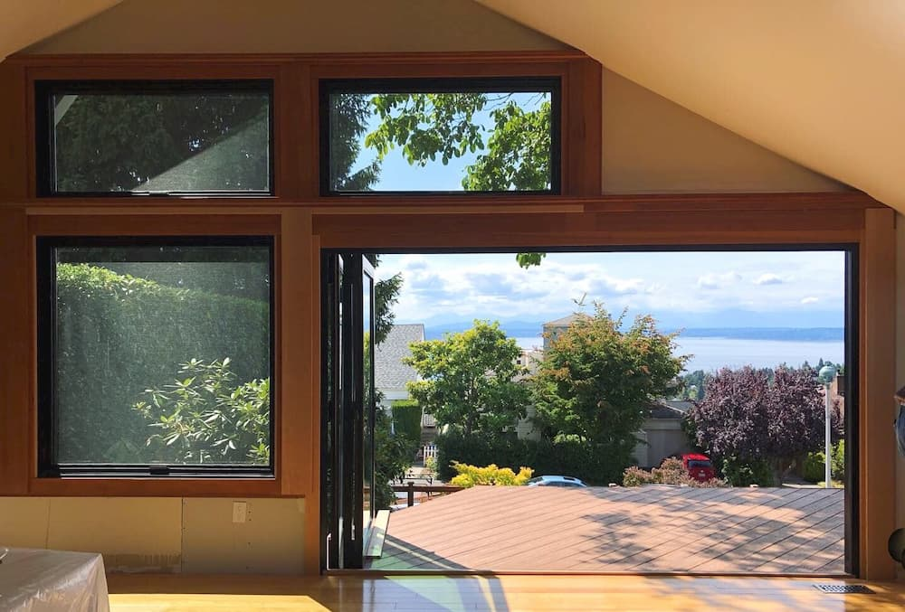 New wood awning windows and a three-panel bi-fold patio door that is open